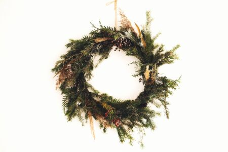 Rustic christmas wreath made of pine branches, cones and berries hanging on white wall. Stylish christmas wreath. Scandinavian minimal decor. Seasons greetings 免版税图像