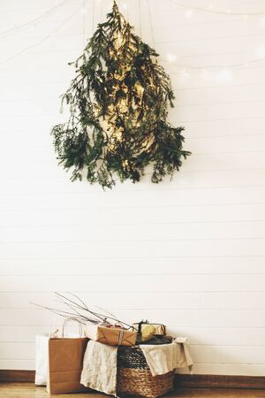 Modern christmas eco tree of pine branches hanging on wall with festive lights and presents in rustic basket. Stylish christmas gift boxes on wooden floor under creative christmas tree. 免版税图像