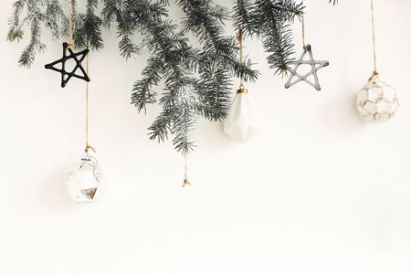 Stylish christmas ornaments on fir branch hanging on white wall. Creative christmas festive decor. Pine branch with vintage glass toys. Modern Scandinavian minimal decoration 免版税图像