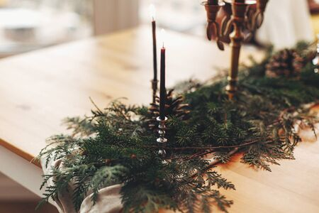 Stylish rustic christmas arrangement for festive dinner. Fir branches with pine cones and vintage candlestick with burning black candles on wooden table. Christmas rural table decor for feast
