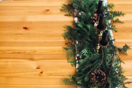 Fir branches with pine cones and vintage candlestick with black candles on wooden table. Copy space. Stylish rustic christmas arrangement for festive dinner. Christmas rural table decor