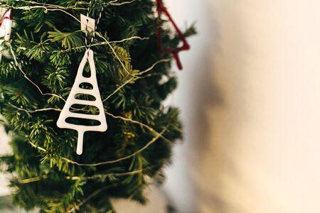 Stylish glass ornaments hanging on christmas tree. Modern glass toy, creative abstract white tree on christmas tree. Festive decor. Scandinavian minimal decoration