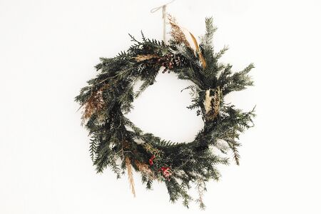 Rustic christmas wreath made of pine branches, cones and berries hanging on white wall. Stylish christmas wreath. Scandinavian minimal decor. Copy space