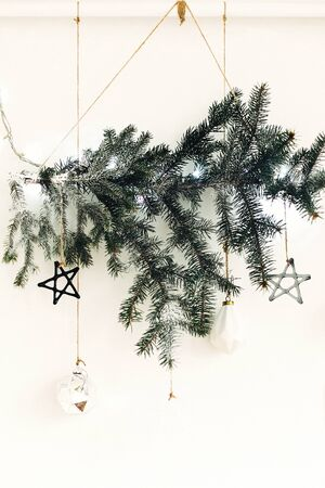 Stylish christmas ornaments hanging on fir branch on white wall. Creative christmas festive decor. Pine branch with vintage glass toys. Scandinavian minimal decoration