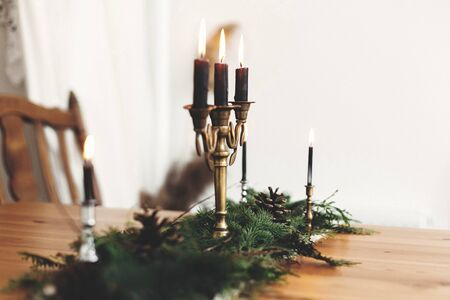 Fir branches with pine cones and vintage candlestick with burning black candles on wooden table. Stylish rustic christmas arrangement for festive dinner. Christmas rural table decor for feast 免版税图像