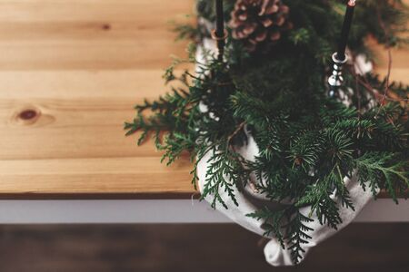 Stylish rustic christmas arrangement for festive dinner closeup. Fir branches with pine cones and vintage candlestick with black candles on linen cloth on wooden table. Christmas rural decor