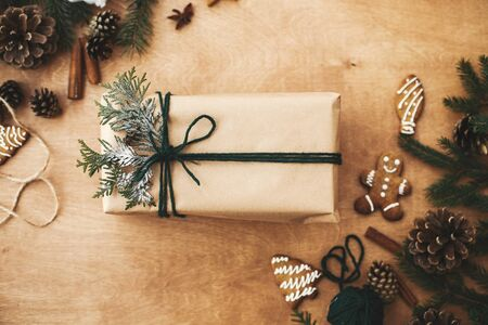 Merry Christmas flat lay. Stylish rustic christmas gifts box with cedar branch on  rural wooden table