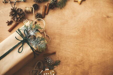 Stylish rustic christmas gifts box with cedar branch on  rural wooden table with pine cones