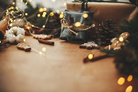 Merry Christmas. Stylish rustic christmas gift in black wrapping paper with cinnamon decoration on background of golden lights, pine branches, cones, gingerbread cookies and cotton.