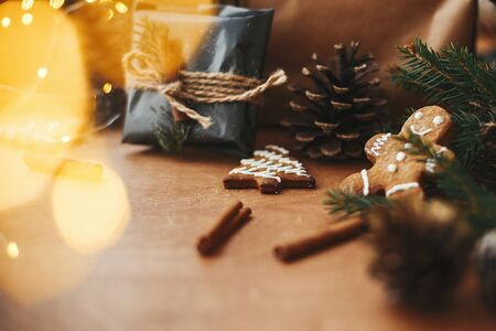 Gingerbread cookies and stylish rustic christmas gift in black wrapping paper