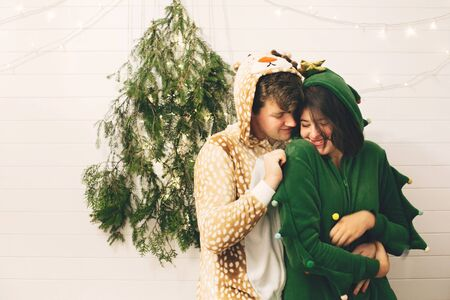 Happy couple in festive pajamas hugging at christmas tree lights in stylish room.