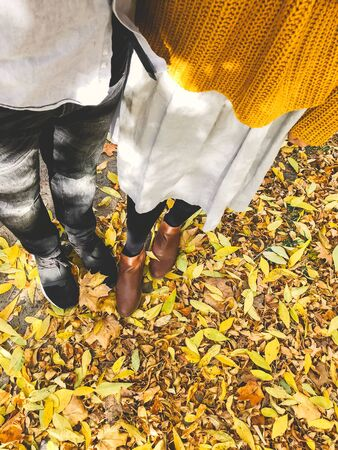 Top view of couples feet in yellow autumn leaves. Stylish hipster couple legs in fall leaves in sunny warm city street. Traveling together. Family on vacation 免版税图像