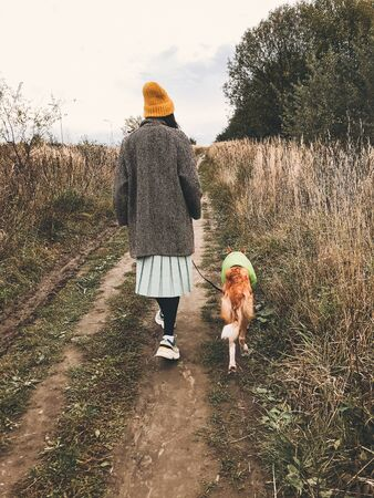 Hipster girl in yellow hat and in coat walking with her golden dog in coat in autumn field among herbs. Stylish woman in modern outfit walking with her friend dog in countryside 免版税图像