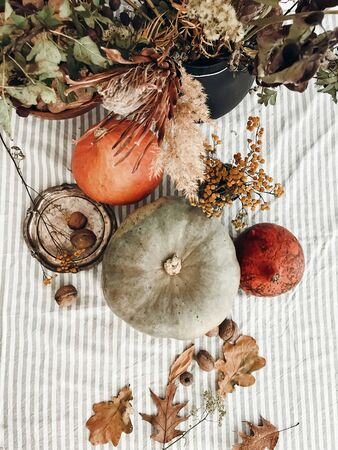 Pumpkins, nuts,yellow flowers, dried herbs, fall leaves on rustic table, top view. Fall decor and arrangement on table. Autumn harvest. Thanksgiving concept