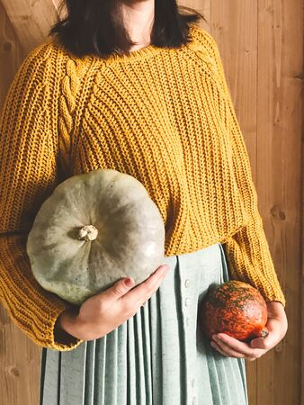 Hipster girl in yellow sweater holding pumpkins on rustic wooden background. Fall rural decor and arrangement. Autumn harvest. Thanksgiving concept. 免版税图像