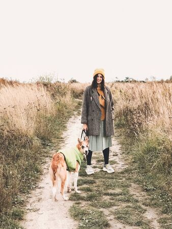 Stylish Hipster girl in yellow hat and coat walking with her golden dog in coat in autumn field among herbs. Woman in modern clothes walking with friend dog in countryside