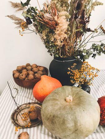 Pumpkins, nuts,yellow flowers, dried herbs, fall leaves on rustic table. Fall decor and arrangement on table. Autumn harvest. Thanksgiving concept