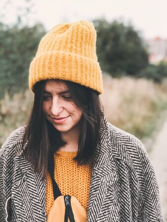 Portrait of beautiful hipster girl in yellow hat and brown coat walking  in autumn field. Woman in modern clothes relaxing in countryside in fall season, face closeup