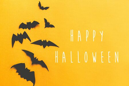 Happy Halloween text, greeting card. Black bats flying on bright yellow paper background. Flat lay. Modern spooky minimal halloween decor. Halloween sign