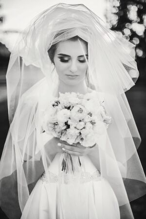 Sensual creative portrait of beautiful bride under veil holding bouquet outdoors. Gorgeous bride in white gown with modern wedding bouquet posing in summer park. Black and white photo Archivio Fotografico - 132303871
