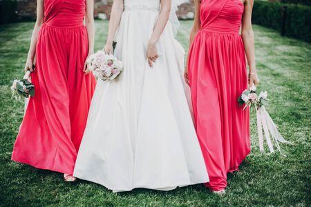 Wunderschöne Braut, die mit Brautjungfern in rosa Kleidern spaziert und stilvolle Blumensträuße im warmen Abendlicht im Sommerpark hält. Schöne glückliche Braut mit Trauzeugin posiert zusammen