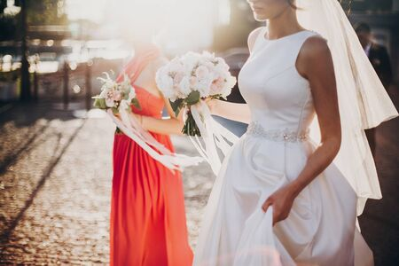 Gorgeous bride walking with bridesmaids, holding stylish bouquets in warm evening light in summer street. Beautiful happy bride with maid of honor walking together