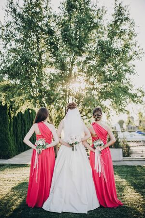 Gorgeous bride posing with bridesmaids in pink dresses, holding stylish bouquets on back in warm evening light in summer park. Beautiful happy bride with maid of honor posing together