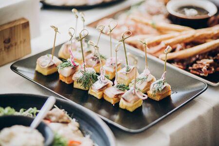 Tavola di cibo delizioso al ricevimento di nozze. Antipasti di bastoncini di pesce con cipolla sul tavolo al matrimonio o alla festa di Natale. Concetto di ristorazione di lusso