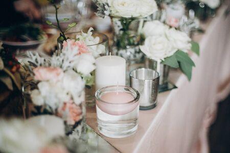 Candela, fiori bianchi in vaso di vetro moderno su centrotavola rosa. Arredamento di lusso alla moda sulla tavola di nozze. Ristorazione e ornamenti di lusso. Festa delle feste Archivio Fotografico