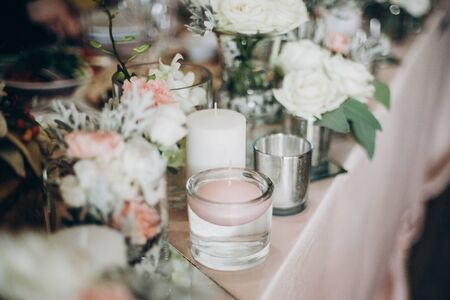 Candle, White  flowers in modern glass vase on pink centerpiece. Stylish luxury decor on wedding table.Luxury catering and adorning. Holiday feast