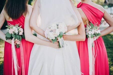 Wunderschöne Braut, die mit Brautjungfern in rosa Kleidern posiert und stilvolle Blumensträuße auf dem Rücken im warmen Abendlicht im Sommerpark hält. Schöne glückliche Braut mit Trauzeugin posiert zusammen Standard-Bild