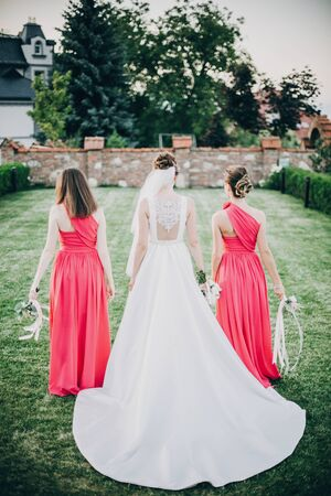 Gorgeous bride walking with bridesmaids in pink dresses, holding stylish bouquets in warm evening light in summer park. Beautiful happy bride with maid of honor posing together