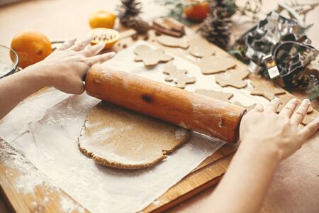 Hands rolling raw dough with wooden rolling pin on background of metal cutters, anise, ginger, cinnamon, pine cones, fir branches on rustic table.Making christmas gingerbread cookies.