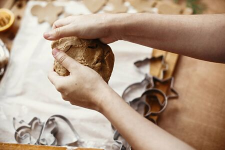 Hands kneading raw dough on background of rolling pin,metal cutters, anise, ginger, cinnamon, pine cones, fir branches on rustic table.Making christmas gingerbread cookies.