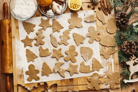 Making christmas gingerbread cookies, flat lay. Raw dough in different shapes cookies and wooden rolling pin, anise, ginger, cinnamon, pine cones, fir branches on rustic table. Imagens