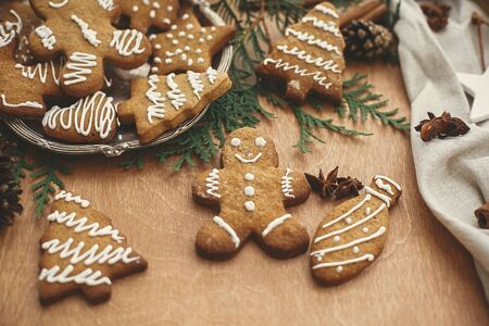 Christmas gingerbread man, cookies on vintage plate and anise, cinnamon, pine cones and cedar branches on rustic table. Baked traditional gingerbread cookies. Seasons greetings
