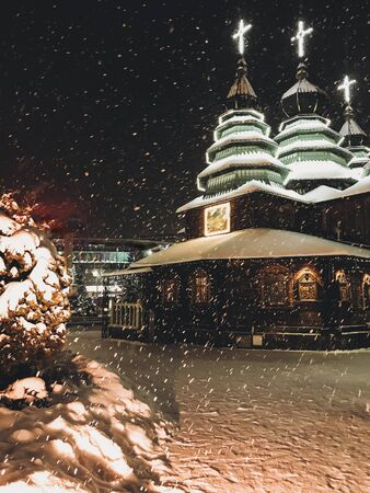 Wooden church with lights and illuminated crosses on tops in snowy night in christmas eve. Christmas evening near christian church in snowy weather, spiritual moment.