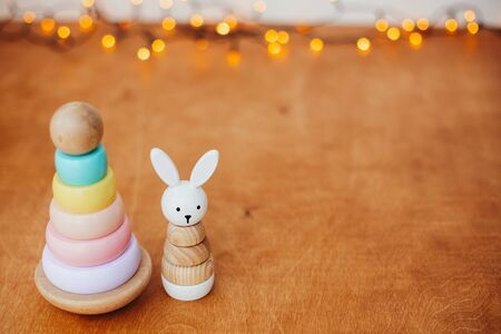 Stylish wooden toys for child on wooden table with lights. Modern colorful wooden pyramid with rings, wooden bunny. Eco friendly plastic free christmas gifts for toddler.