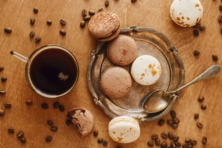 Coffee in glass cup and delicious macaroon cookies on vintage plate on wooden table with roasted coffee beans. Flat lay. Morning coffee and breakfast. Espresso with sweets