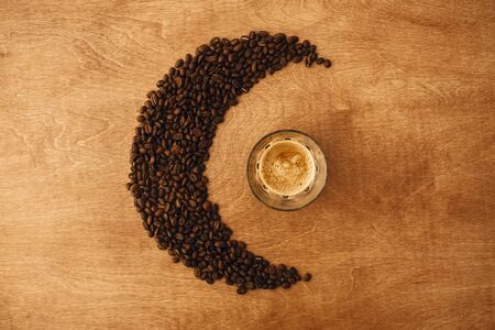 Hot espresso with foam in glass cup and aromatic roasted coffee beans in shape of moon on wooden table. Flat lay, Copy space. Alternative Coffee brewing concept. Creative photo