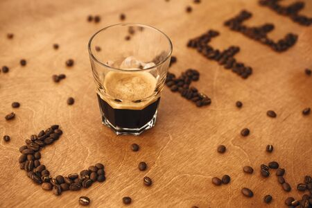 Coffee word made of aromatic roasted coffee beans and glass cup of hot espresso on wooden table, copy space. International coffee day. Coffee text Stock fotó