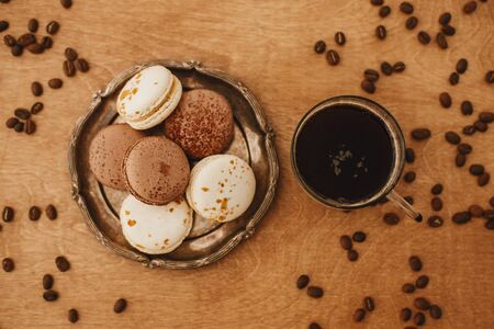 Coffee in glass cup and delicious macaron cookies on vintage plate on wooden table with roasted coffee beans. Flat lay. Morning coffee and breakfast. Espresso with sweets