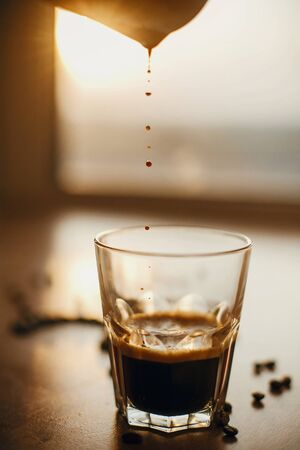 Pouring hot espresso in glass cup  in warm light on background of  aromatic roasted coffee beans on wooden table.  Alternative Coffee brewing concept. Copy space Stock fotó