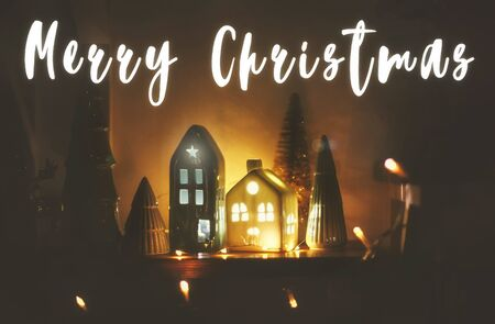 Merry Christmas text sign. Seasons greeting card. New Year. Christmas little houses with lights and trees in christmas evening.