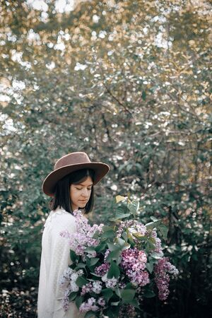 Stylish boho woman in hat holding lilac flowers bouquet in sunny spring park. Calm portrait of beautiful hipster girl standing with purple lilac in spring garden. Copy space