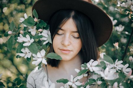 Sensual portrait of beautiful hipster woman in hat  in white spring flowers. Stylish calm boho girl posing in blooming tree with flowers in sunny spring park. Copy space