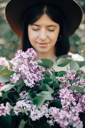 Big Lilac flowers bouquet in hands of stylish boho woman in hat in sunny spring park. Calm portrait of beautiful hipster girl standing with purple lilac in spring garden. Copy space