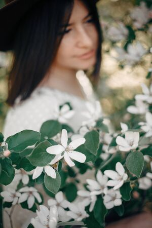 Quince white flowers on tree branch on background of blurred boho girl enjoying aroma from tree in spring garden. Cydonia oblonga tree blooming in spring orchard farm Zdjęcie Seryjne