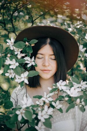 Calm portrait of beautiful hipster girl standing in white blooms in spring. Stylish boho woman in hat posing in blooming tree with white flowers in sunny spring park.