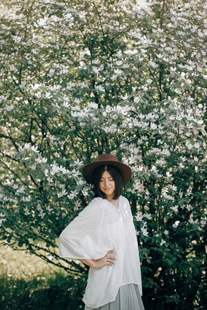 Stylish boho woman in hat posing in blooming tree with white flowers in sunny spring park. Calm portrait of beautiful hipster girl standing in white blooms in spring